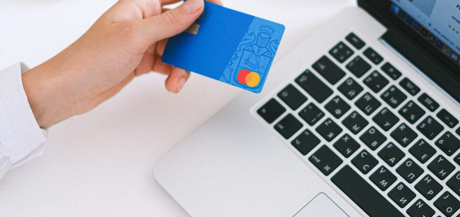 hands holding a credit card and using a laptop