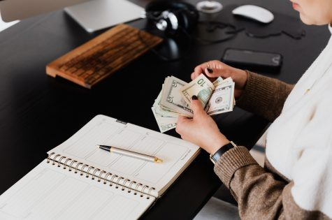Woman counting money and budgeting at desk
