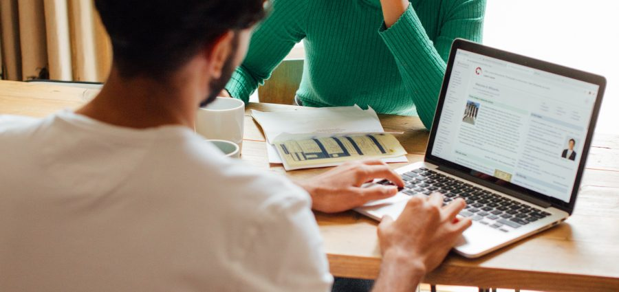 Man working on laptop sitting at a table with woman