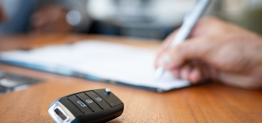 Car key on desk with person signing contract