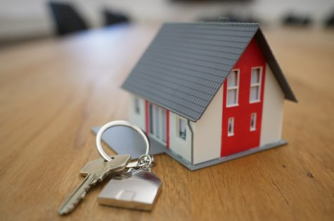 Miniature home with keys laying on table