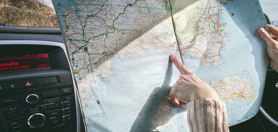 person pointing to spot on road map in car