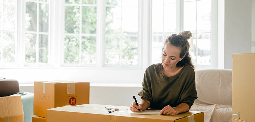young woman writing on packing box
