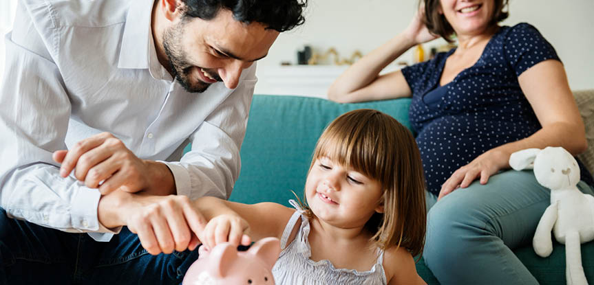 Mother and father teaching young girl to save with piggy bank
