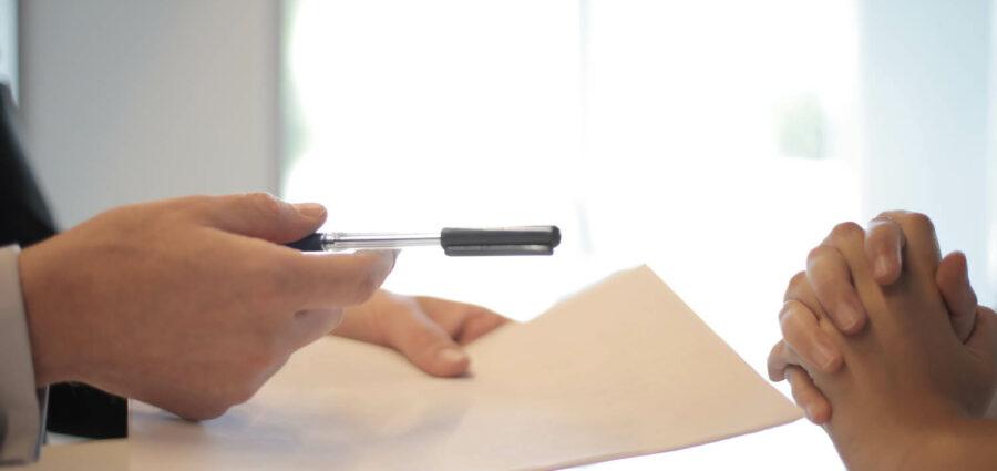 man handing woman a pen to sign a paper