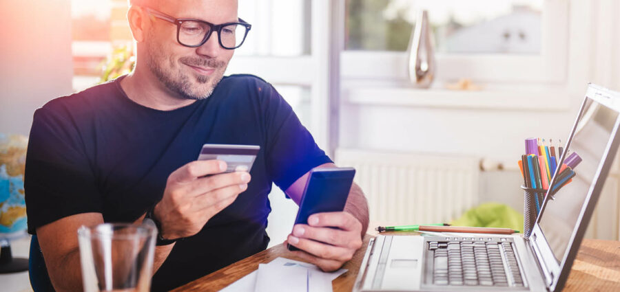 photo man paying with credit card on smart phone at home office